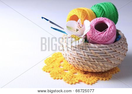 Colorful clews and crochet hooks in wicker basket on wooden background