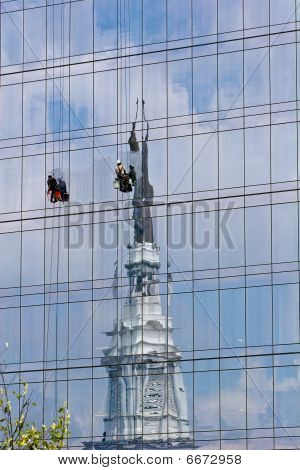 Window Washers On Building With Church Reflection