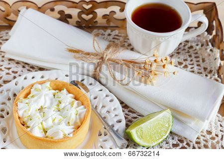 Lemon Tart Pie On  Plate With Tea Cup Spoon Serviette Tray With Fresh Lime