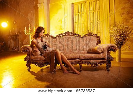 Luxury young woman in expensive interior. Young girl with flawless makeup and evening volume hairstyle.
