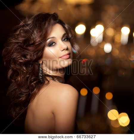 Luxury young woman in expensive interior. Girl with flawless makeup and evening volume hairstyle.