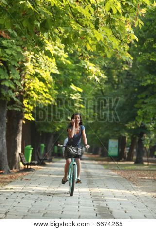 Woman On The Phone Riding Bicycle