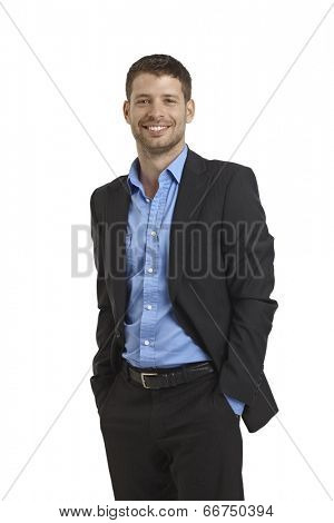 Happy young businessman standing with hands in pockets.