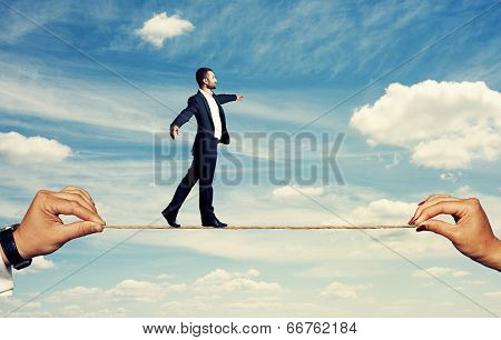 smiley businessman walking on the rope at outdoor