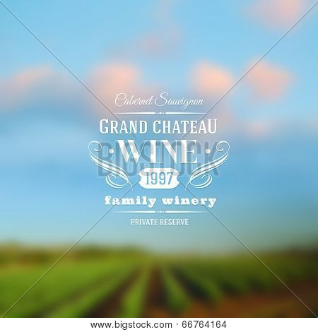 Wine label type design against a vineyards landscape defocused background
