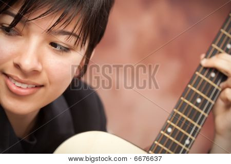 Attractive Ethnic Girl Plays Guitar