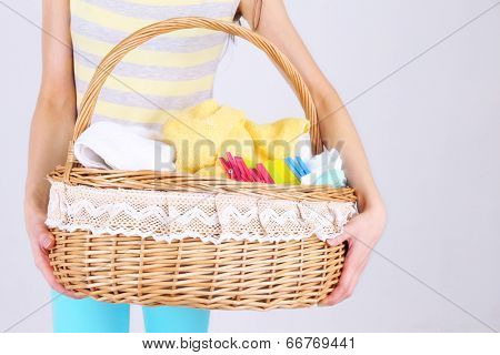 Woman holding laundry basket with clean clothes, towels and pins, on gray background