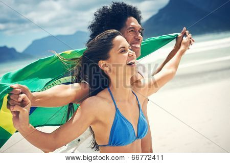 Latino hispanic couple are Brasil fans and hold flag having fun together