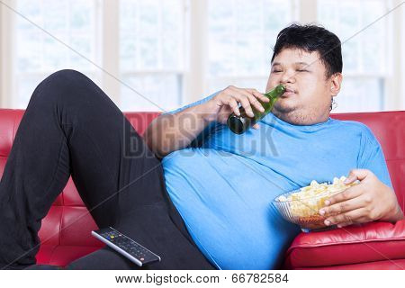 Overweight Man Sitting Lazy On Sofa