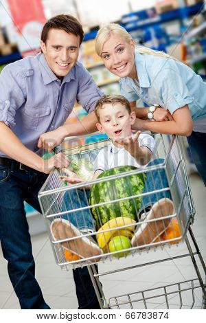 Family drives cart with food and son sitting there with watermelon. Concept of fresh and healthy food and consumerism