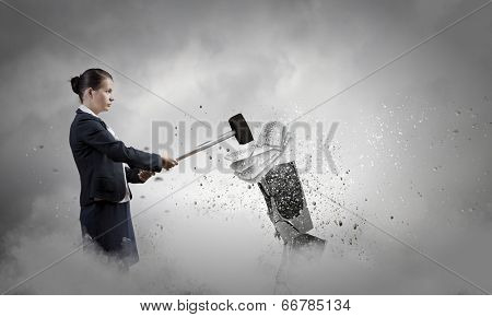 Businesswoman in anger crashing keyboard with hammer