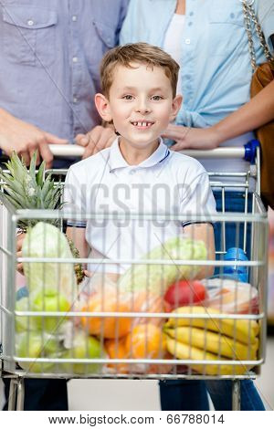 Family drives shopping trolley with food and boy sitting there. Concept of fresh and healthy food and consumerism