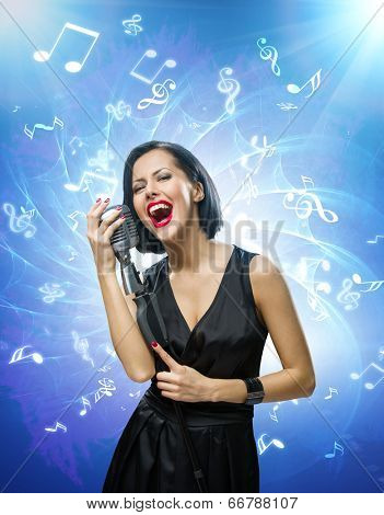 Half-length portrait of female musician wearing black evening dress and keeping mike on blue music background with notes. Concept of music and retro fashion