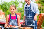 stock photo of grilled sausage  - Father and daughter making barbecue in the garden in summer with sausages and meat - JPG