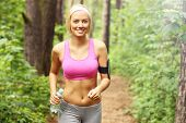 stock photo of bottle water  - A picture of a woman jogging in the forest with a bottle of water - JPG