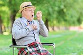 stock photo of asthma  - Senior man having an asthma attack in a park - JPG