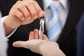 stock photo of crop  - Cropped image of estate agent giving house keys to man in office - JPG