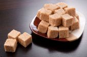 stock photo of sugar cube  - Brown sugar cubes on plate and black background - JPG