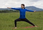 pic of virabhadrasana  - Man is doing a variation of Warrior pose in yoga outdoors - JPG
