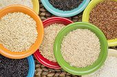 stock photo of ceramic bowl  - a variety of rice grains on colorful ceramic bowls against a woven water hyacinth mat - JPG