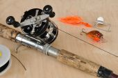 stock photo of fishing rod  - Rod and Baitcasting Reel and Other Fishing Gear on a Board - JPG