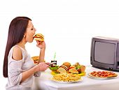 image of high calorie foods  - Woman eating fast food and watching TV - JPG