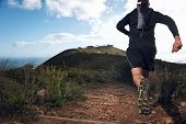 picture of crossed legs  - trail running man on mountain path exercising - JPG