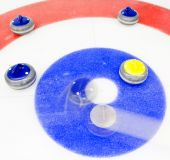 pic of bounce house  - Blue stone taking the house by tapping away a yellow stone at a curling game - JPG