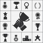 image of trophy  - Set of black silhouette vector trophy and award icons with cups  ribbons  rosettes  stars  podium  medals  medallions and a hand holding aloft a large trophy in the centre in celebration of a victory - JPG