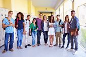 stock photo of ten years old  - Group Of High School Students Standing In Corridor - JPG