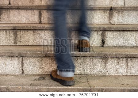Man Walking Up An Old Stone Staircase