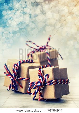Three handmade gift boxes in shiny colour christmas background.