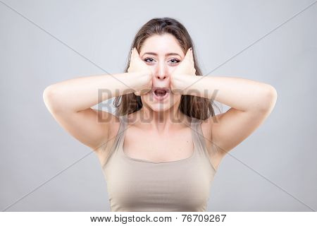 Beautiful young  woman doing face yoga