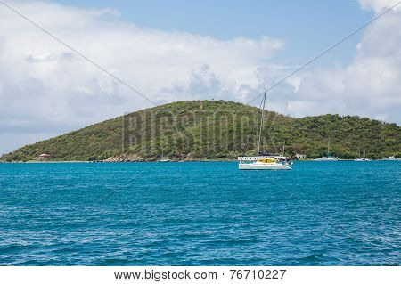 Catamaran In Blue Water By Green Hills