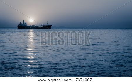 Moon Rising Above A Sailing Cargo Ship