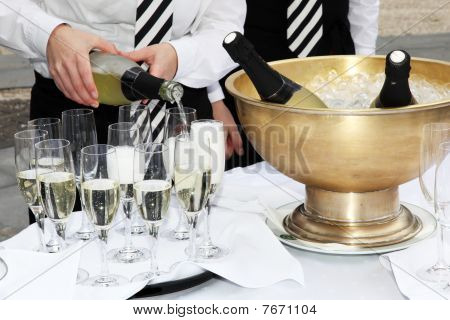 Two Waiters Fill Glasses Of Champagne