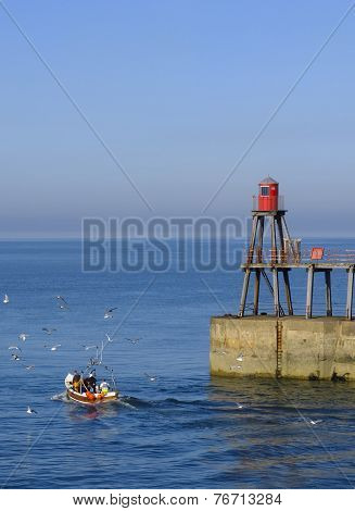 Local fishing boat leaving Whitby Harbour , England