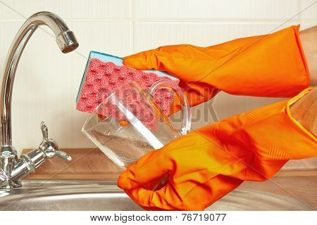 Hands in gloves with sponge and dirty glass over the sink in kitchen