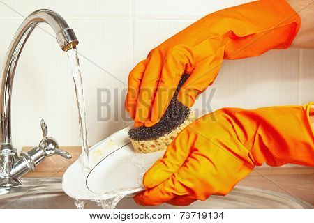 Hands in gloves wash the dirty dishes under running water in kitchen