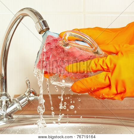 Hands in rubber gloves with sponge wash glass under running water