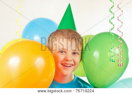 Little boy in holiday cap with festive balls and streamer