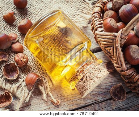 Bottle Of Nut Oil And Basket With Filberts On Old Kitchen Table.