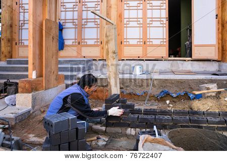 JEONJU, SOUTH KOREA - 03 NOVEMBER 2014: A traditional brick layer constructs a brick wall to extend the house. This traditional building method is still used in the rural parts of South Korea.