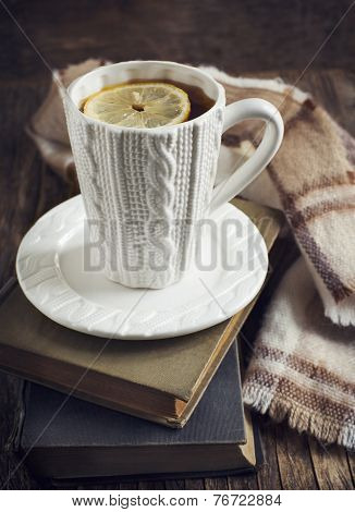 Cup Of Hot Tea With Lemon, Books And Scarf On Wooden Table