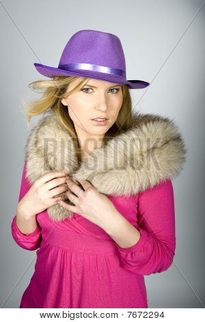 young beautiful elegant woman with violet hat and fur.gray background