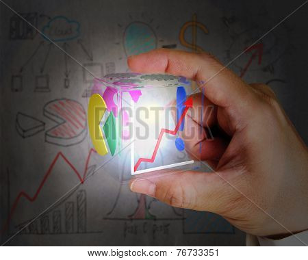 Hand Holding Glowing Colorful Glass Cube On Dark Doodles Wall