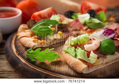 Delicious italian pizza primavera served on wooden table, close-up.
