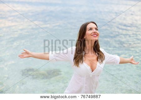 Woman relaxing at the beach with arms open enjoying her freedom,  independence, good health, time off.