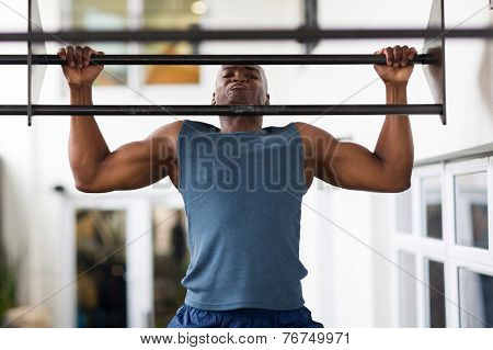 strong african man doing pull-ups on a bar in a gym