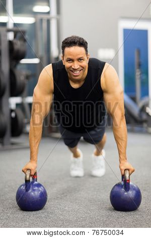 fit mid age man in plank position with kettle bells at the gym